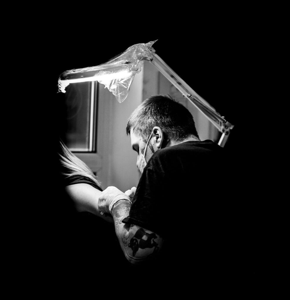 Maciek Czerwiński, tatuażysta oraz wokalista zespołu Ździry, podczas pracy w swoim studio tatuażu, fot. Łukasz Skiera